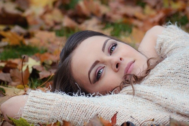 Girl relaxing on the ground in the fall with leaves around her.