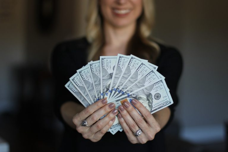 A woman holding a large amount of cash.