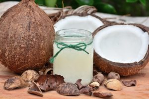 Coconuts next to a jar of coconut oil