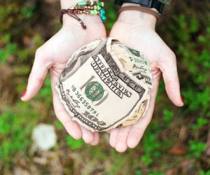 A person holding a globe of money